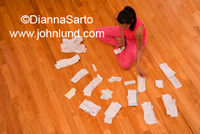 Hispanic woman sitting on the floor surrounded by reciepts and paperwork as she works on her personal finances. She is working on her tax preparation.
